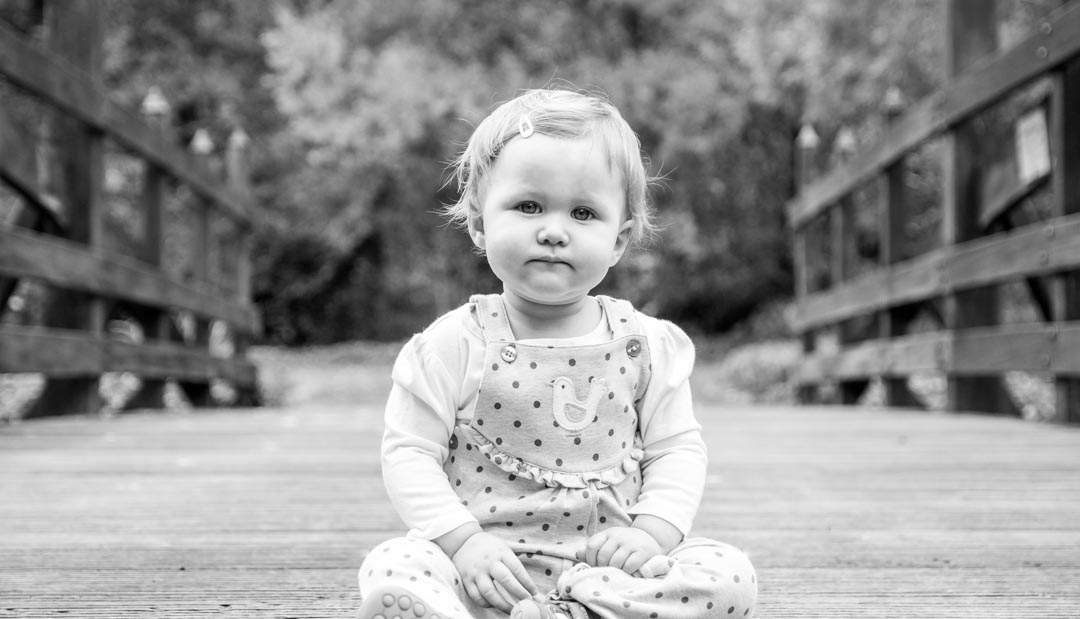 An image of a little girl looking thoughtful - first birthday photoshoot by Sam of Hansford Carter, a Kent wedding photographer