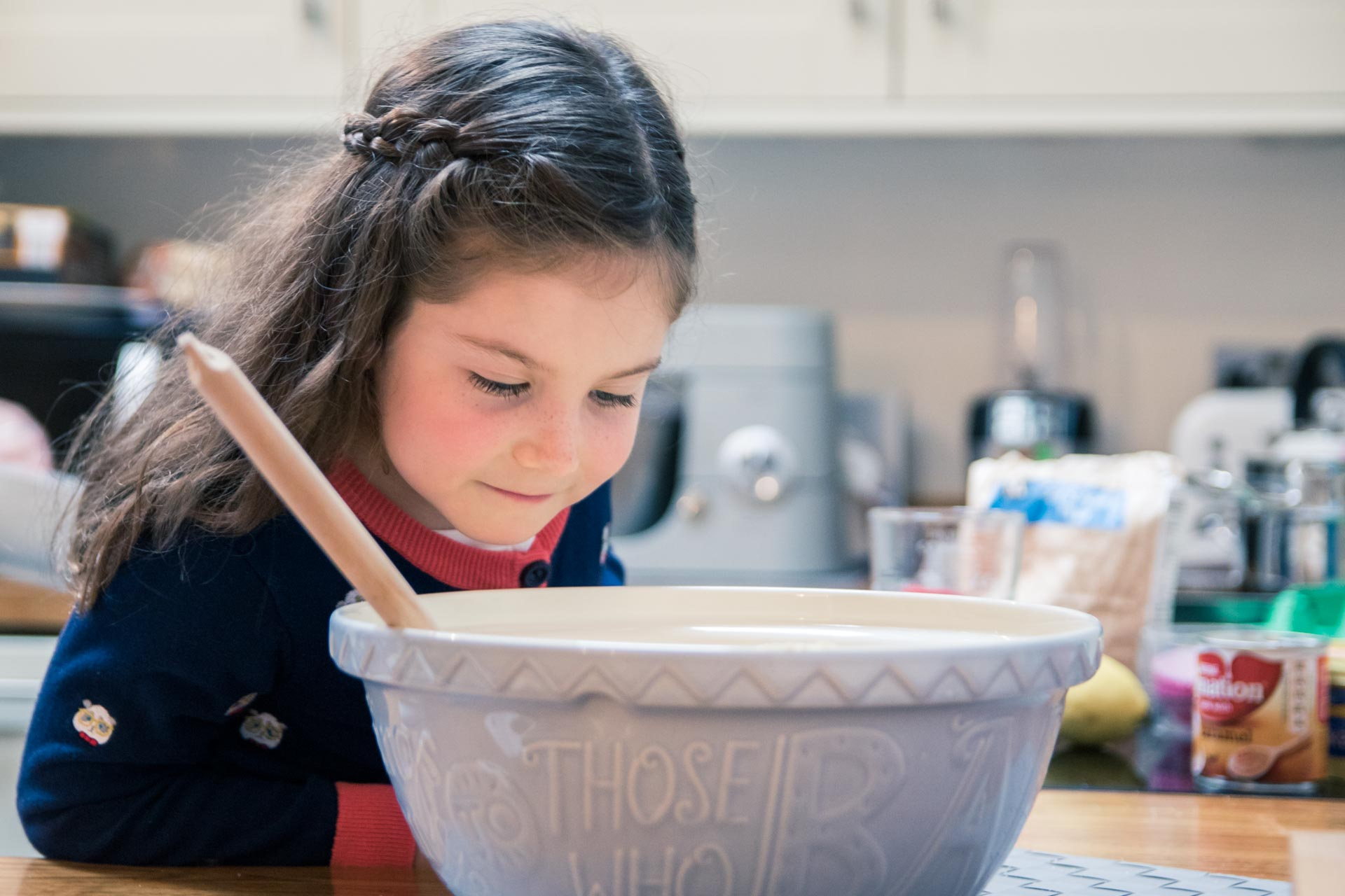 An image of a little girl looking at baking ingredients - family fun baking by Sam of Hansford Carter, a Kent wedding photographer