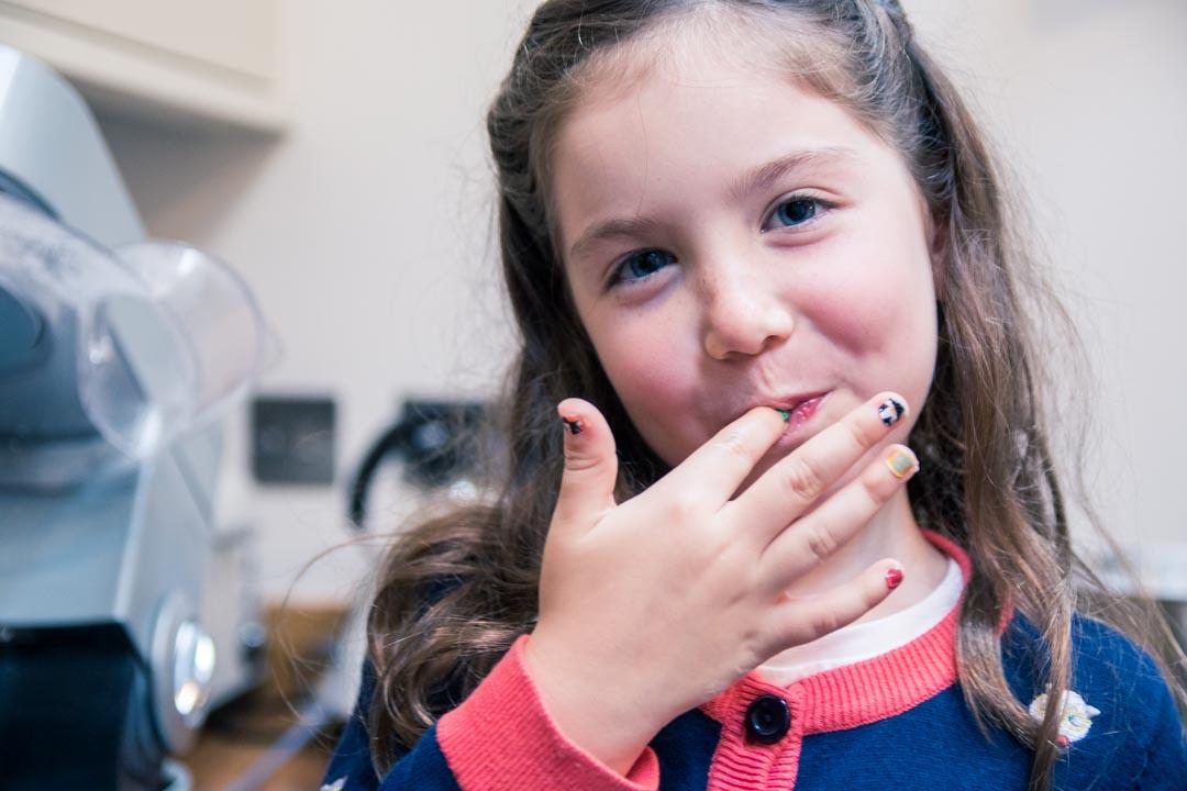 An image of a little girl enjoying eating baking mixture - family fun baking by Sam of Hansford Carter, a Kent wedding photographer