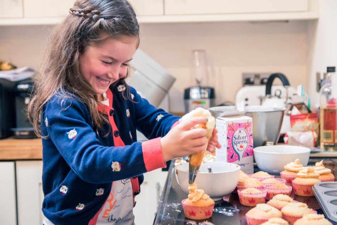 An image of a little girl decorating cupcakes - family fun baking by Sam of Hansford Carter, a Kent wedding photographer