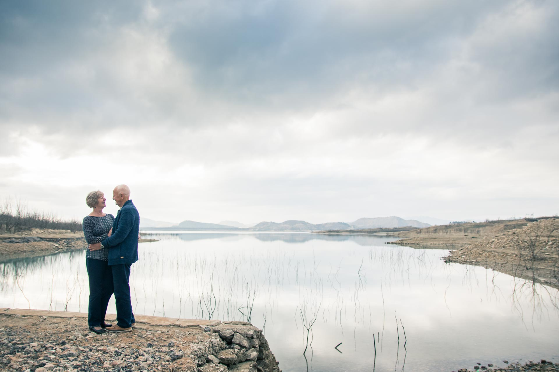 An image of the happy couple stood overlooking a beautiful reservoir - wedding photography by Sam of Hansford Carter, a Kent wedding photographer