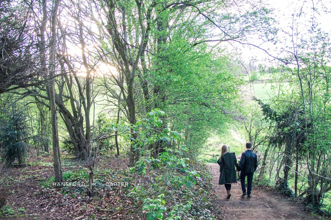 An image of Kirsty and Wayne walking through the woods - wedding photography by Sam of Hansford Carter, a Kent wedding photographer