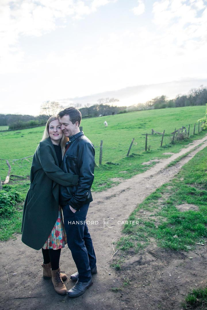 An image of Kirsty and Wayne cuddling by a field - wedding photography by Sam of Hansford Carter, a Kent wedding photographer