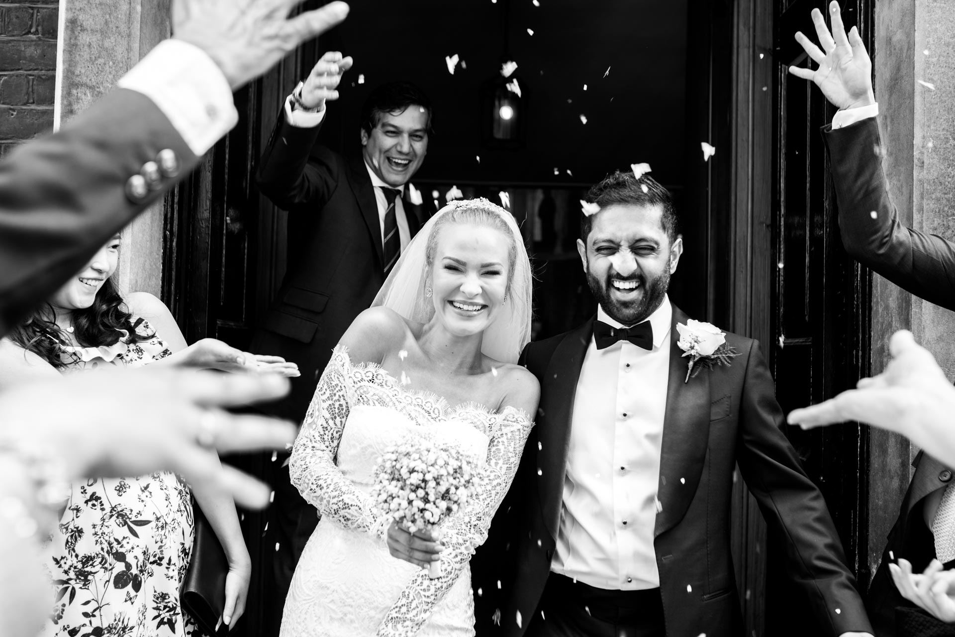 An image of confetti being thrown on the happy couple - wedding photography by Sam of Hansford Carter, a Kent wedding photographer