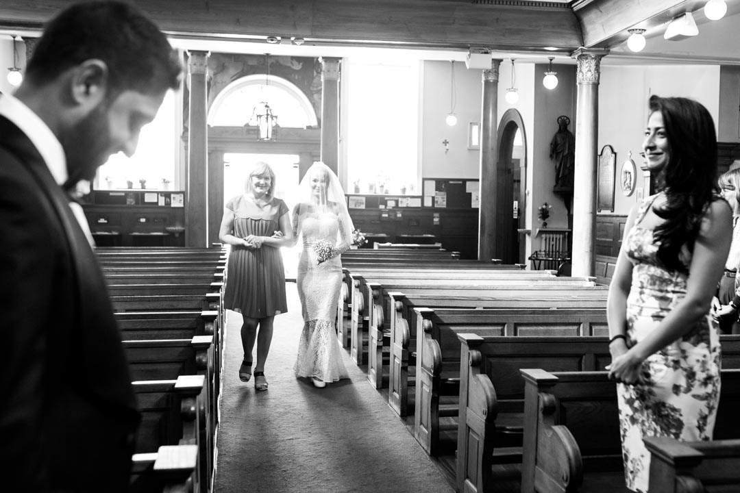 An image of the bride walking down the aisle - wedding photography by Sam of Hansford Carter, a Kent wedding photographer