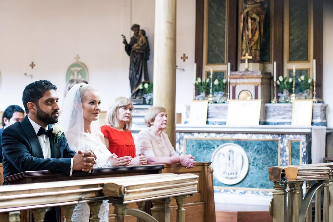 An image of the couple and their guests taking Mass - wedding photography by Sam of Hansford Carter, a Kent wedding photographer