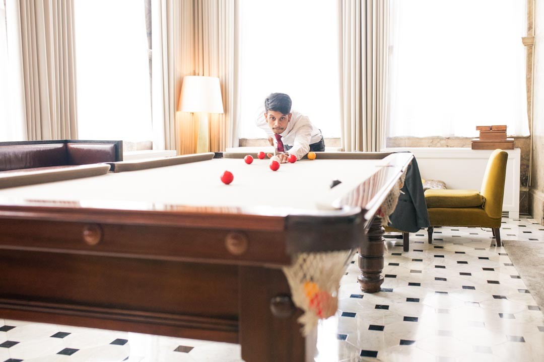 An image of a guest playing pool at the lunch reception - wedding photography by Sam of Hansford Carter, a Kent wedding photographer