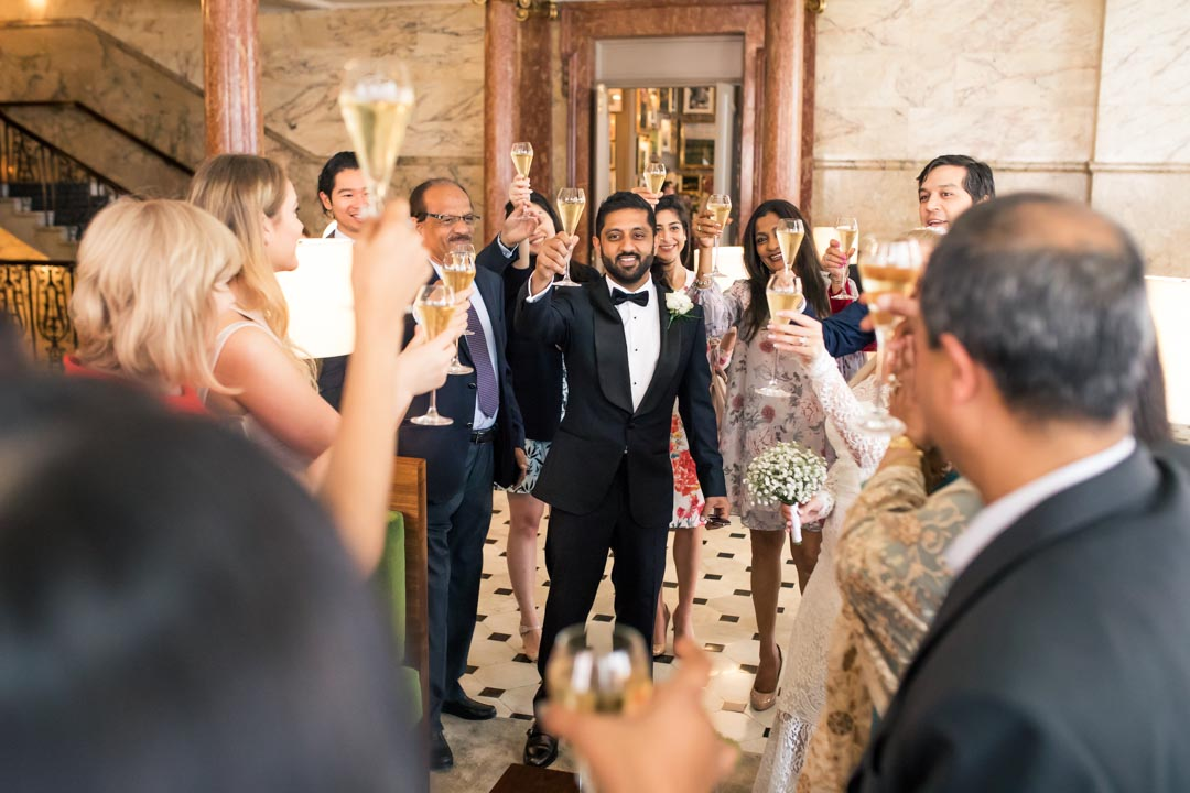 An image of the guests toasting the happy couple - wedding photography by Sam of Hansford Carter, a Kent wedding photographer