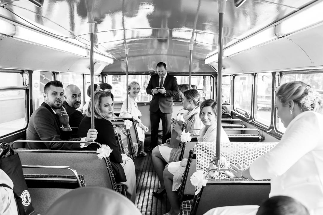 An image of the guests in the vintage bus - wedding photography by Sam of Hansford Carter, a Kent wedding photographer