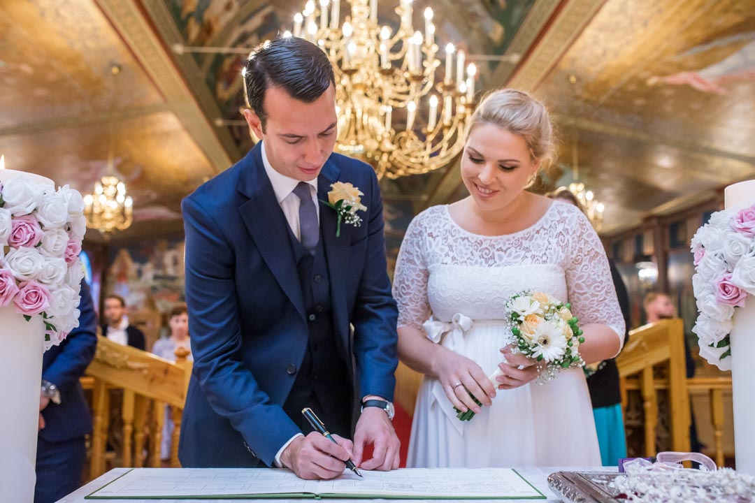 An image of the happy couple signing the register - wedding photography by Sam of Hansford Carter, a Kent wedding photographer