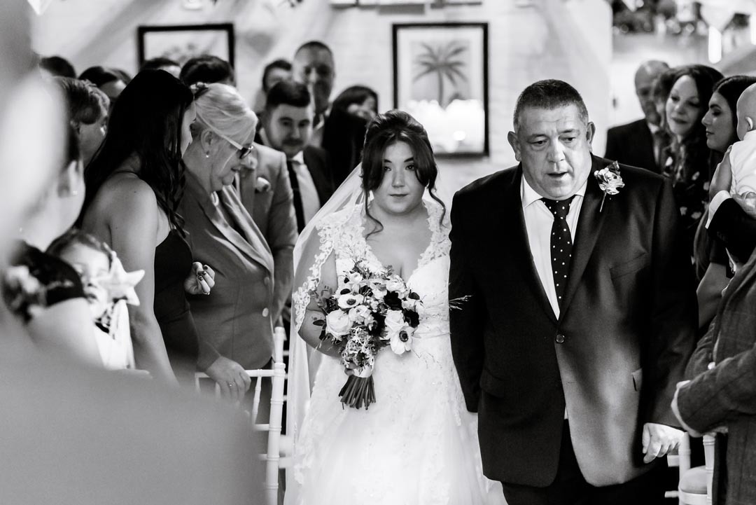 An image of the bride's father walking her down the aisle - wedding photography by Sam of Hansford Carter, a Kent-based wedding photographer