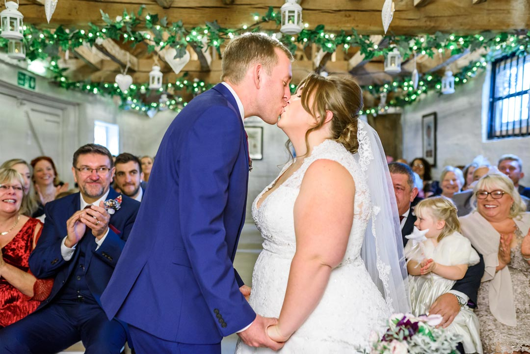 An image of the couple's first kiss - wedding photography by Sam of Hansford Carter, a Kent-based wedding photographer