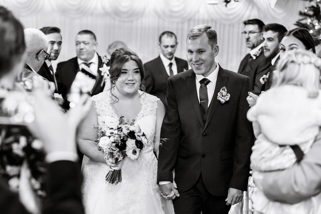 An image of the happy couple walking together down the aisle - wedding photography by Sam of Hansford Carter, a Kent-based wedding photographer