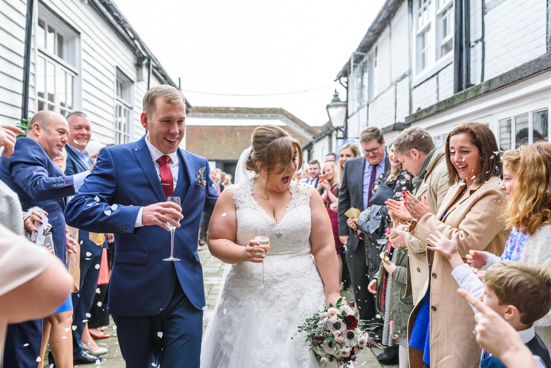 An image of the happy couple during the confetti throw - wedding photography by Sam of Hansford Carter, a Kent-based wedding photographer