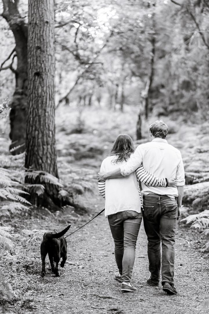 An image of a couple walking through the woods with their dog - couple shoot by Sam of Hansford Carter, a Kent-based wedding photographer