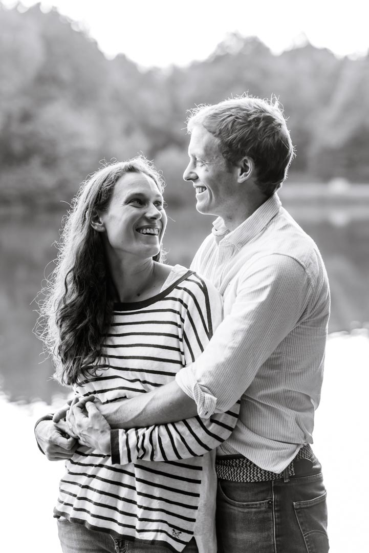 An image of a couple laughing together by a lake - couple shoot by Sam of Hansford Carter, a Kent-based wedding photographer