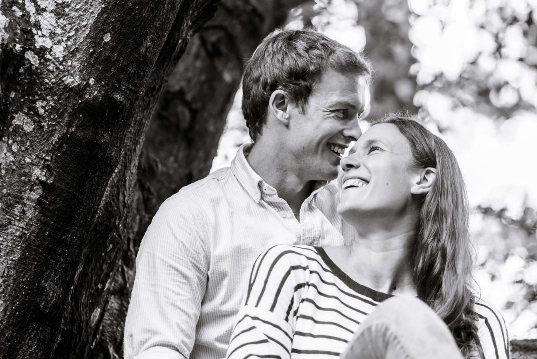 An image of a couple sat in a tree laughing together - couple shoot by Sam of Hansford Carter, a Kent-based wedding photographer