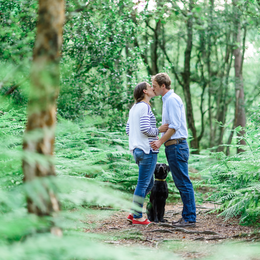 An image of a couple kissing in the woods - couple shoot by Sam of Hansford Carter, a Kent-based wedding photographer