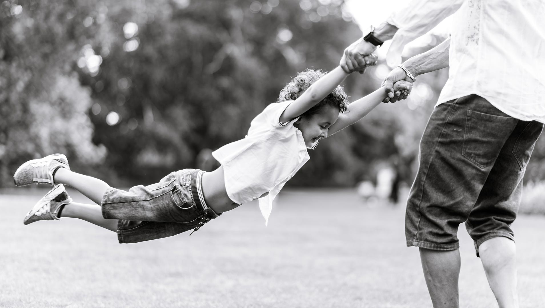 An image of a father swinging his son around - family shoot by Sam of Hansford Carter, a Kent-based wedding photographer