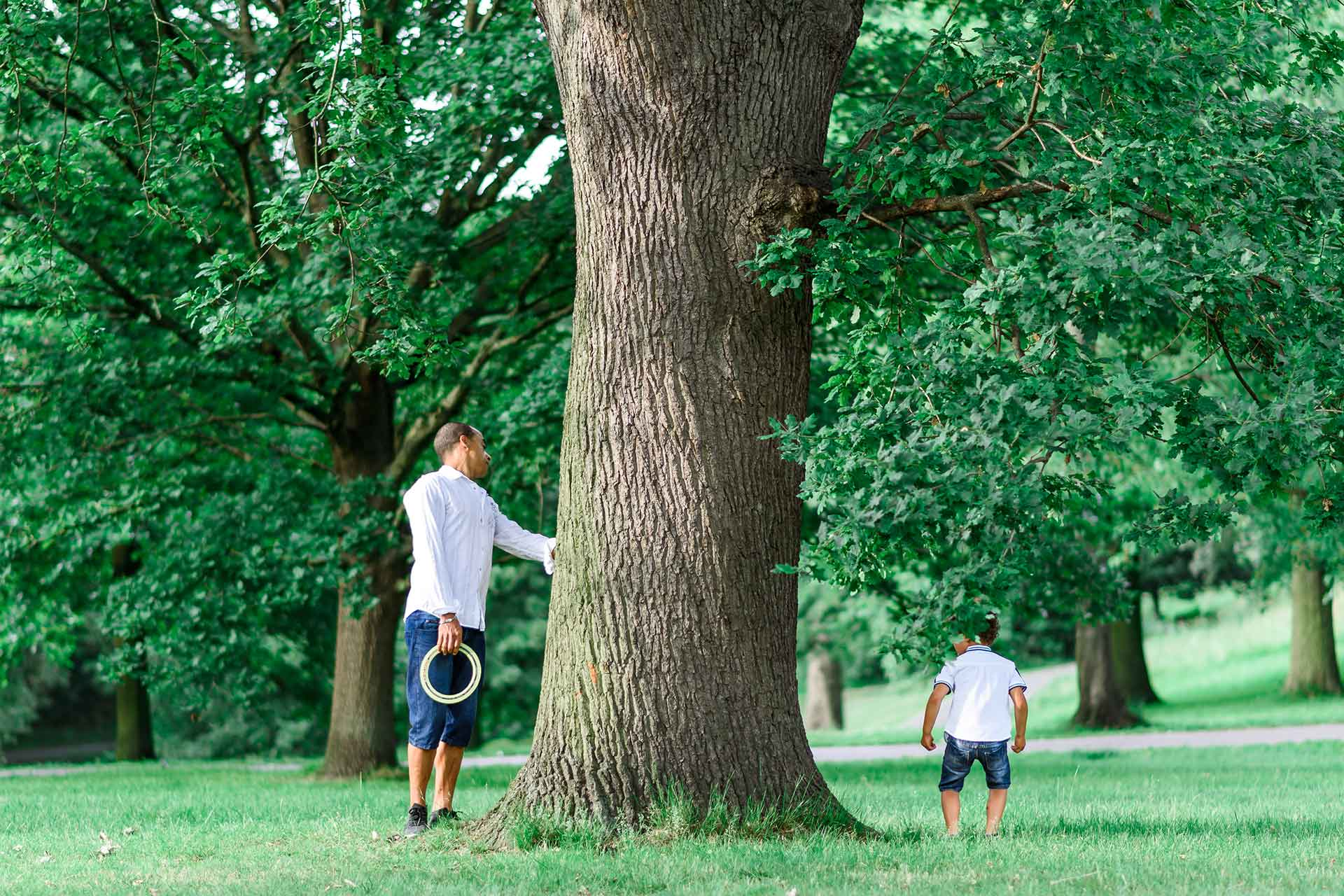 An image of a father and son playing hide and seek - family shoot by Sam of Hansford Carter, a Kent-based wedding photographer