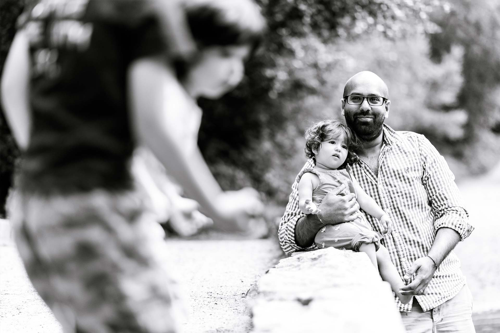 An image of a father holding his daughter whilst watching his sons playing - family shoot by Sam of Hansford Carter, a Kent-based wedding photographer