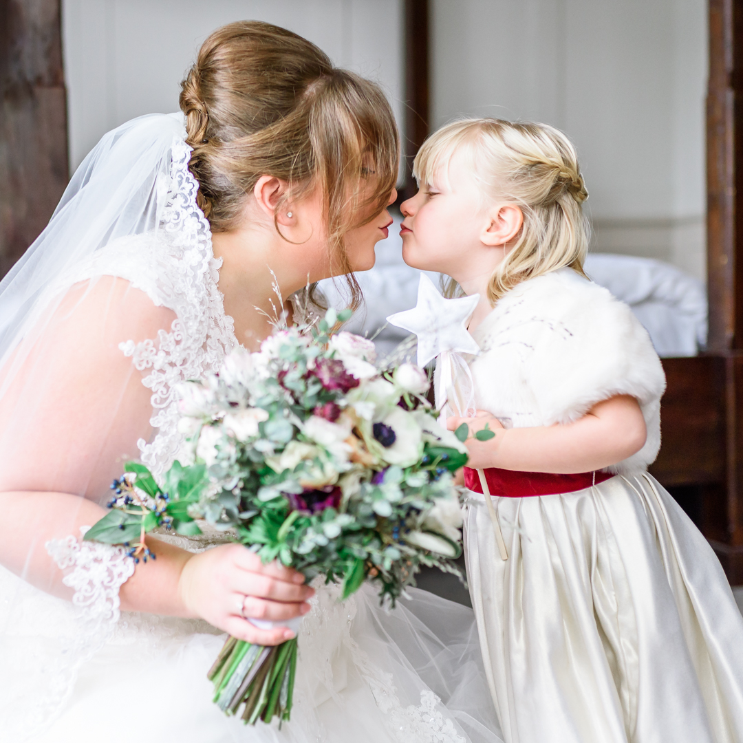 An image of a mother and daughter kissing on a wedding day - wedding day photography by Sam of Hansford Carter, a Kent-based wedding photographer