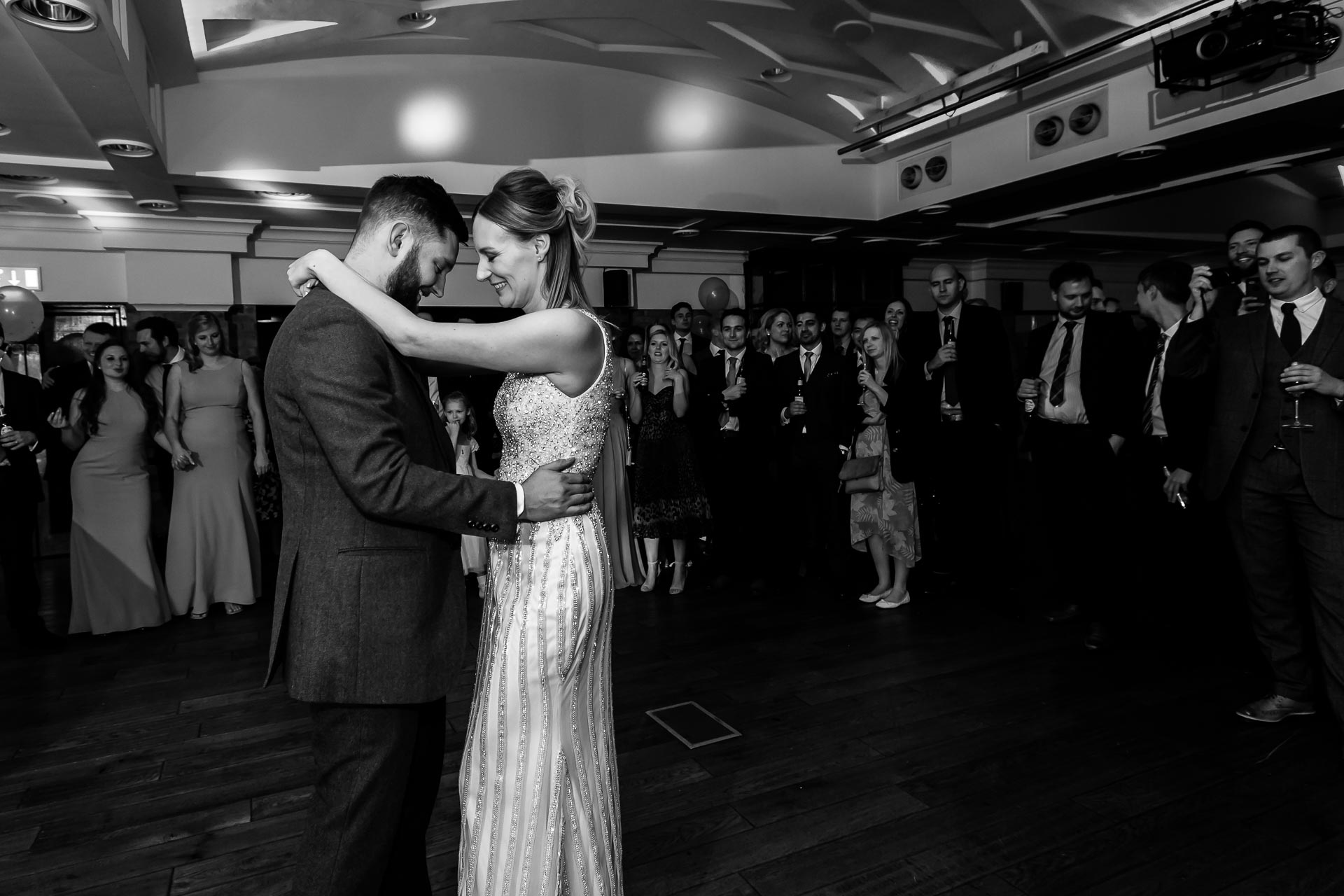 An image of a happy couple dancing their first dance on their wedding day - wedding day photography by Sam of Hansford Carter, a Kent-based wedding photographer