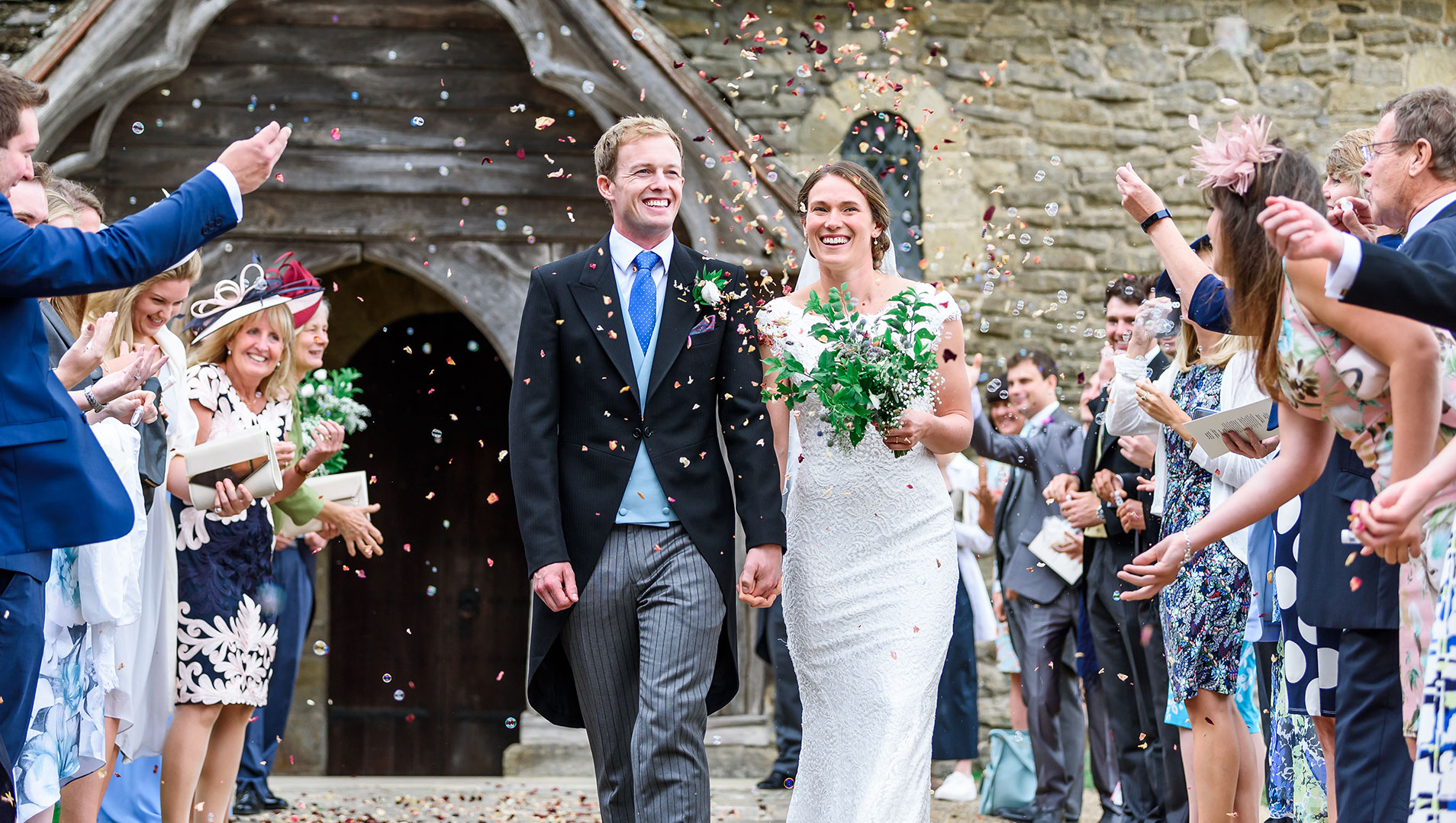 An image of a confetti throw outside a church on their wedding day - wedding day photography by Sam of Hansford Carter, a Kent-based wedding photographer
