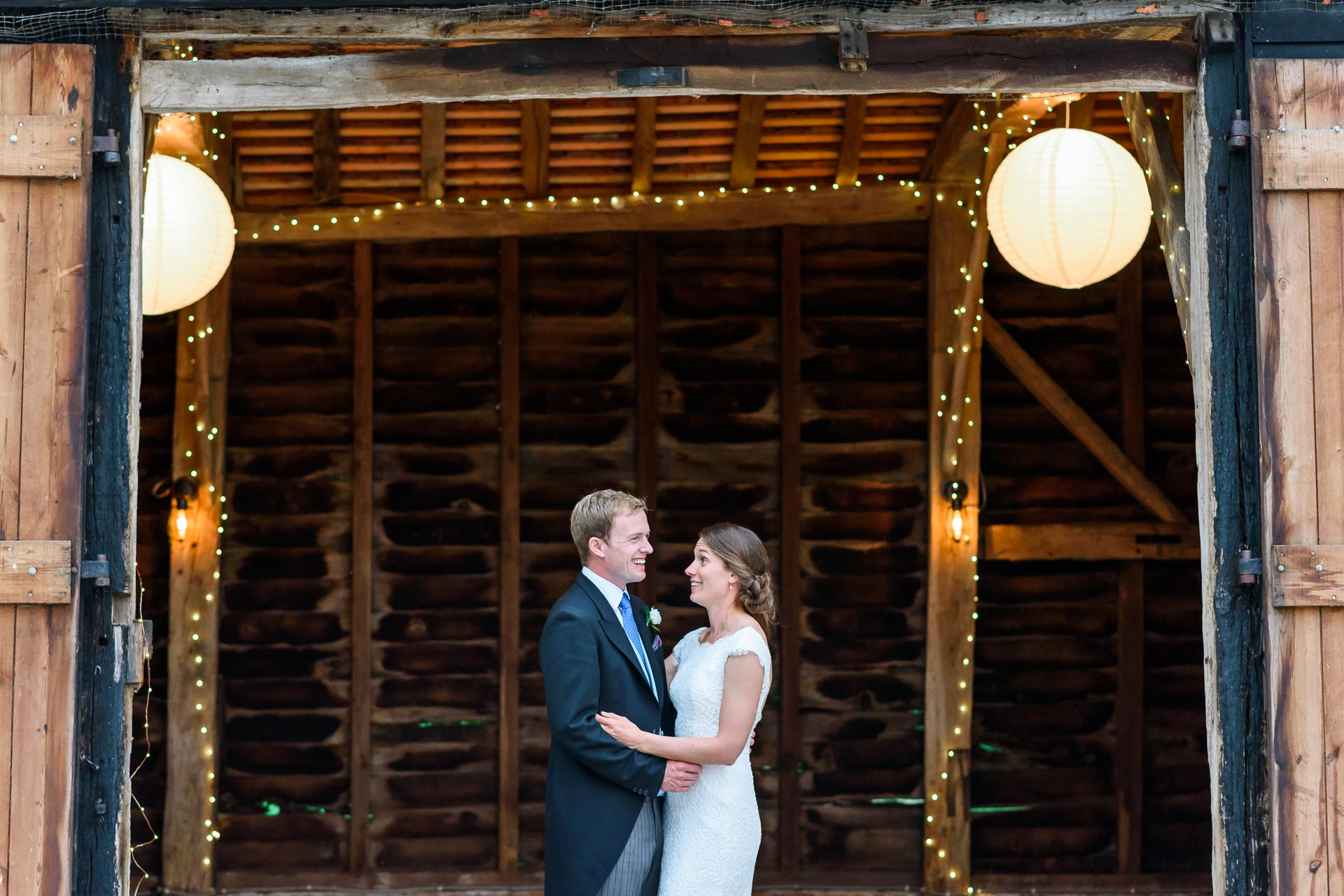 An image of a happy couple together outside their barn reception - wedding day photography by Sam of Hansford Carter, a Kent-based wedding photographer